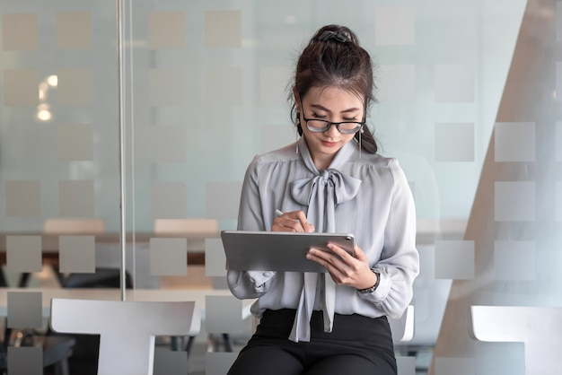 Image of a woman holding tablet sitting and waiting in the office job interview