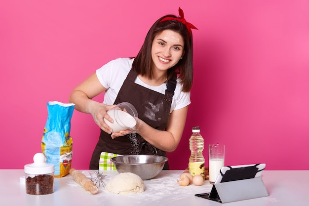 Image of woman making and preparing pastry in bakery kitchen. adding flour bits. female has pleasant facial expession, looks happilly directly at camera, baking bread, dressed brown apron and t shirt.