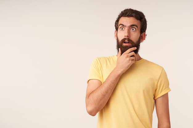 Image of wondering handsome bearded young man fingers touch beard looking aside up emotion surprised or questioning against white wall