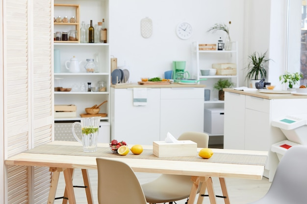 Image of wooden kitchen table with lemonade and fruits on it in domestic kitchen