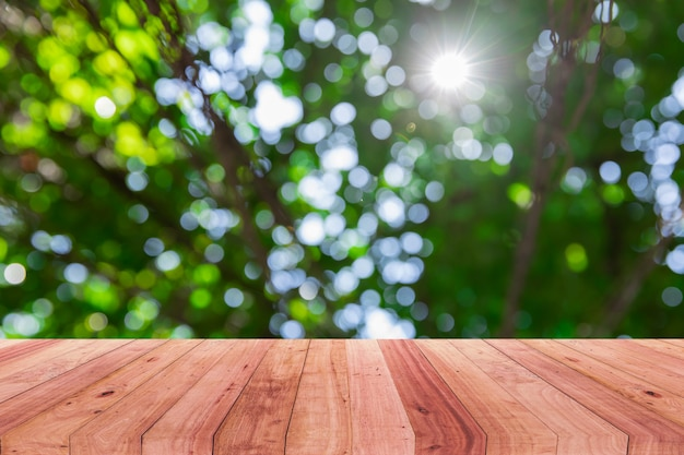 Image of wooden table in front of abstract  background of bokeh nature