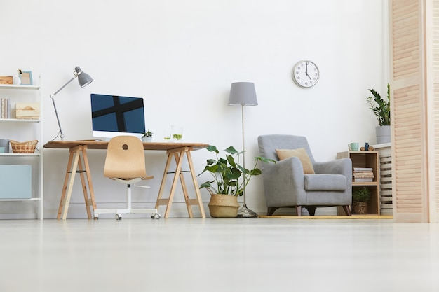 Image of workplace with computer monitor and armchair in the living room at home