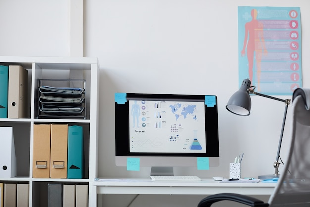 Image of workplace with computer monitor on it and medical posters on the wall at office