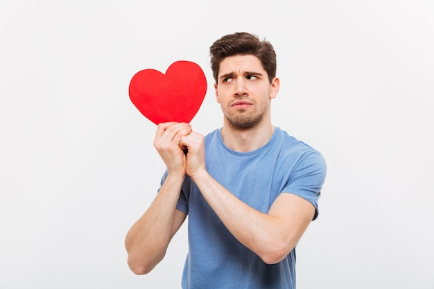 Image of worried man in t-shirt holding paper heart