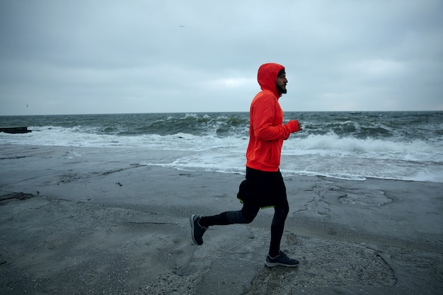 Image of young active bearded male doing morning exercises by sea, running along seafront on cold gloomy weather, wearing warm athletic clothes. fitness male model