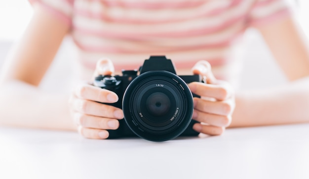 Image of young asian woman holding camera