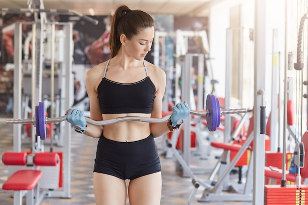 Image of young athletics girl training hard with barbell in gym.