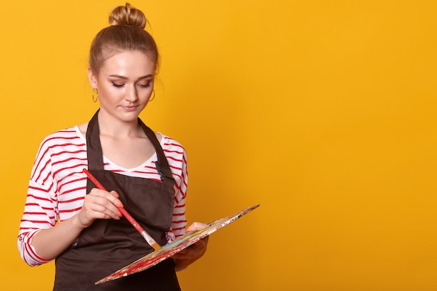 Image of young attentive amateur artist posing with art equipment in both hands