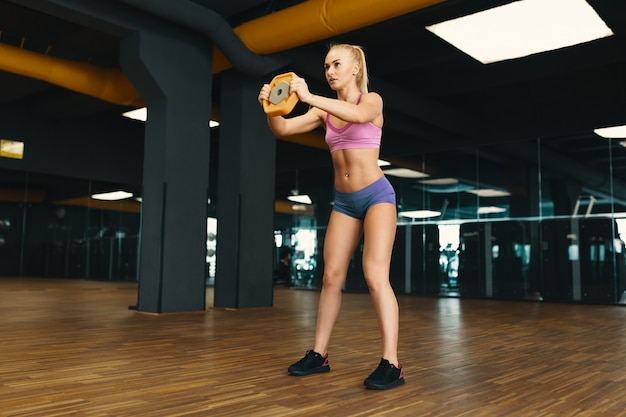 Image of young attractive female in mini shorts doing exercise