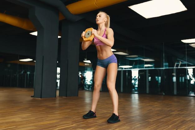 Immagine di giovane femmina attraente in mini pantaloncini facendo esercizio