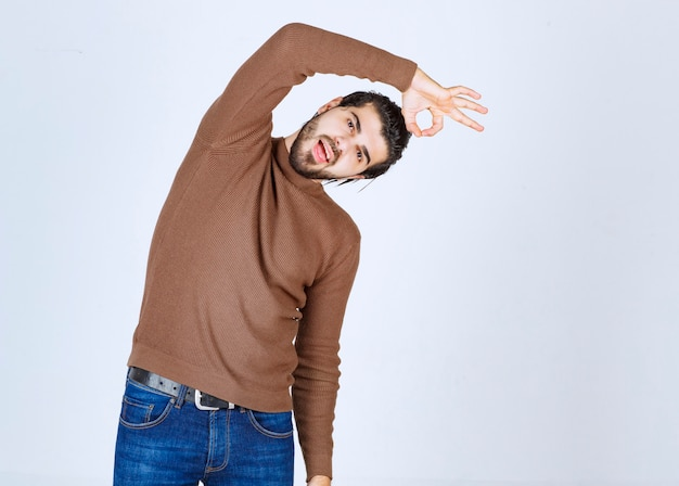 Image of young attractive man dressed in brown sweater showing ok gesture