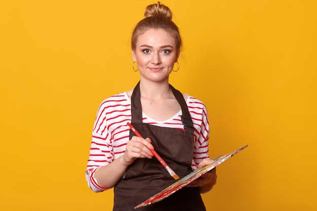 Image of young attractive pleasant wearing stripped sweatshirt, brown apron and earrings, holding paint equipment