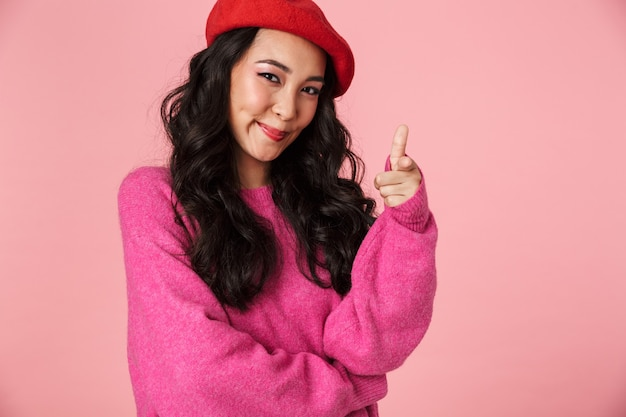 Image of young beautiful asian girl wearing beret smiling and pointing finger at you