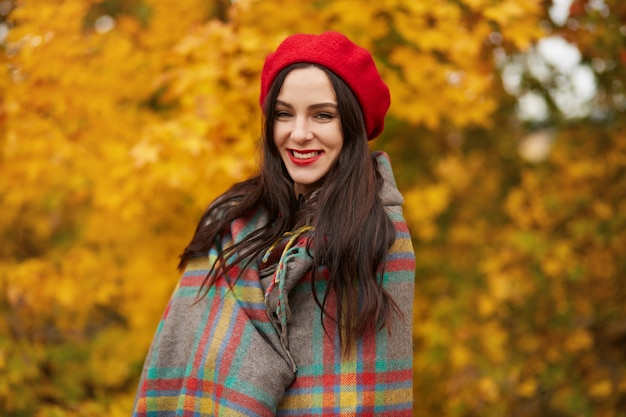 Image of young beautiful brunette woman wrapped in checkered blanket or plaid walks outdoors through autumn park surrounded