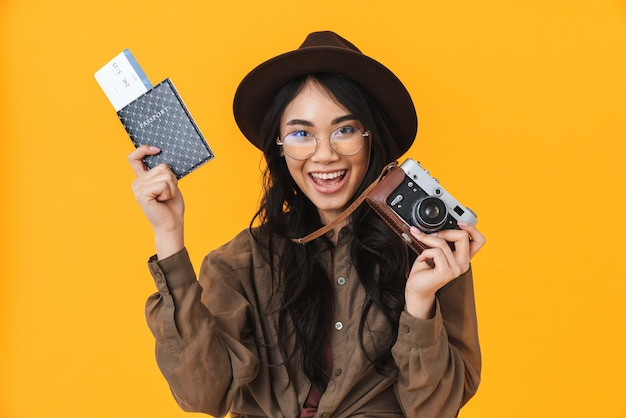 Image of young brunette asian tourist woman wearing hat holding retro camera and travel tickets isolated on yellow