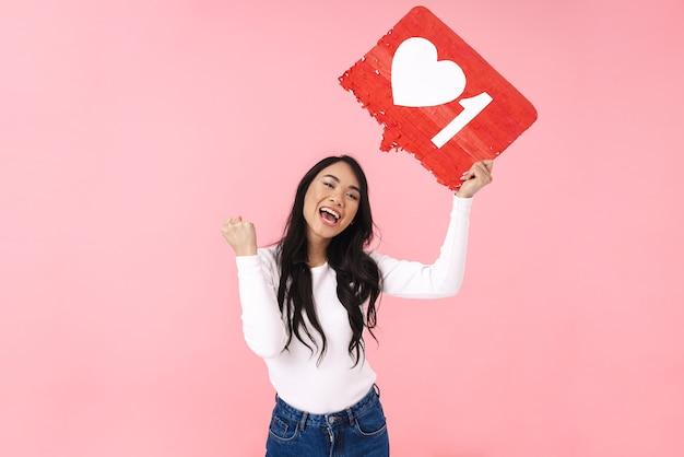 Image of young brunette asian woman wearing eyeglasses holding heart like symbol on placard isolated on pink