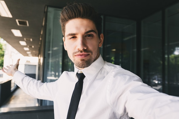 Image of young businessman dressed in formal suit standing outside glass building, and taking selfie photo