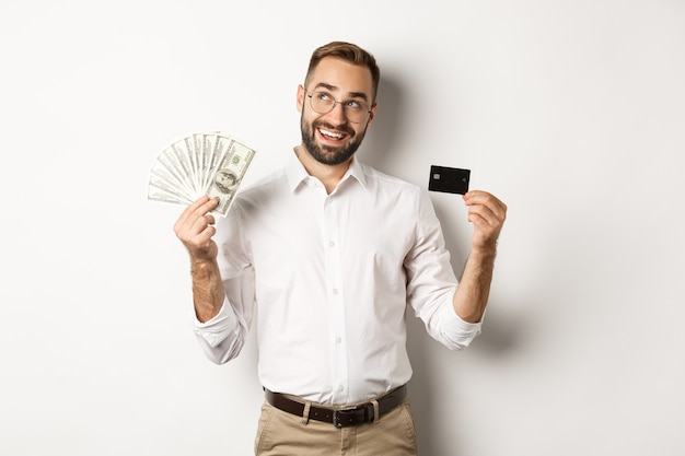 Image of young businessman holding credit card and money, looking at upper left corner and thinking about shopping, standing over white background.