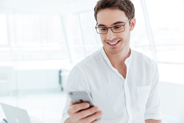 Image of young cheerful man dressed in white shirt chatting by phone. looking at phone.