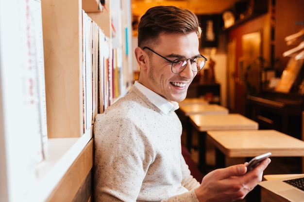 Image of young cheerful man wearing glasses sitting in cafe while using mobile phone.
