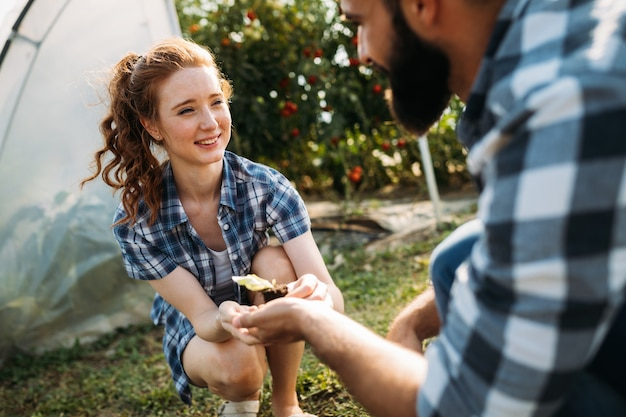 Image of young couple of farmers seedling sprouts in garden