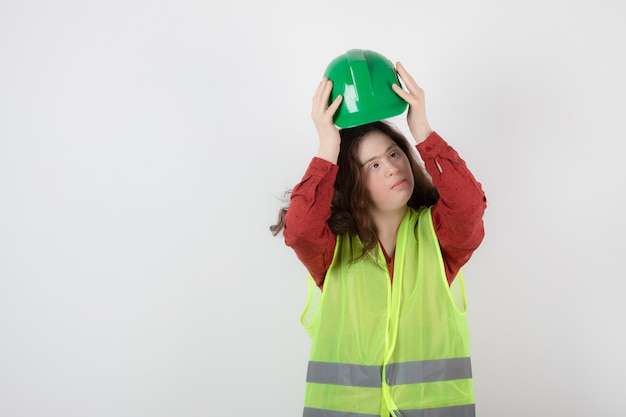 Image of a young cute girl standing in vest and wearing a crash helmet .