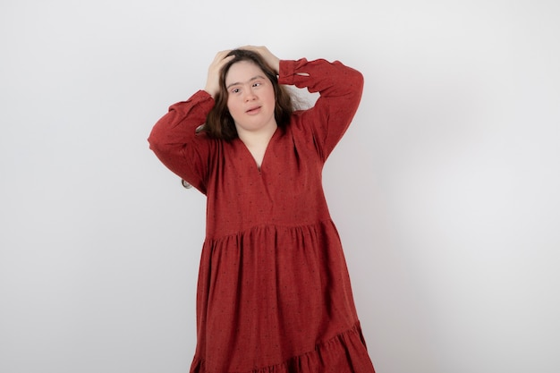 Image of a young cute girl with down syndrome standing and posing .