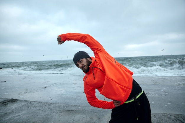 Image of young dark haired sporty man with beard doing physical exercises over seaside background on grey cold morning, stretching muscules before workout. fitness male model
