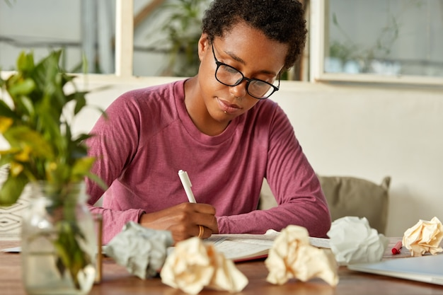 Image of young dark skinned teacher prepares for conducting lesson at college, makes notes in notepad, surrounded with paper balls, has creative chaos on table, focused down, wears optical glasses