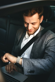 Image of young director man in suit working on laptop and looking at wrist watch, while back sitting in business class car with safety belt