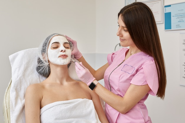 Image of young female with face peeling mask, spa beauty treatment. woman getting facial care by beautician at spa salon. cosmetologist applies cosmetic agent with special brush. skin care concept.