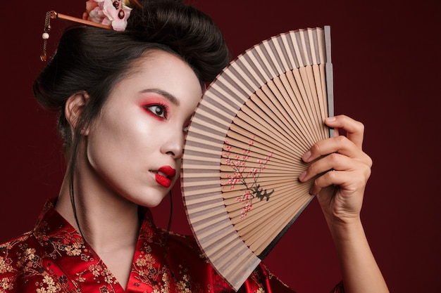 Image of young geisha woman in traditional japanese kimono holding wooden hand fan