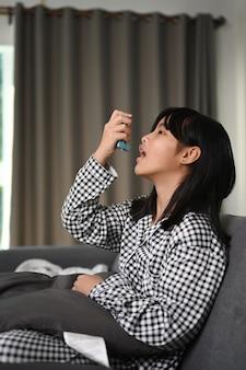 Изображение молодой девушки, использующей ингалятор для лечения астмы, сидя на диване у себя дома.