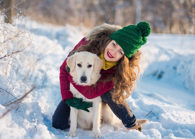 Image of young girl with her dog white golden retriever hugging, outdoor at winter time
