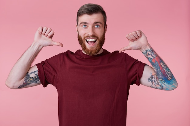 Image of young handsome bearded man with tattooed hand, smiles broadly and looking at the camera, pointing fingers at himself because he is the best, isolated over pink background.