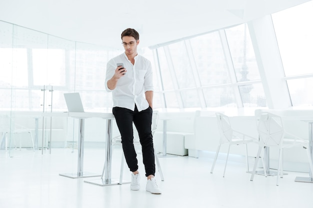 Image of young handsome man dressed in white shirt using mobile phone. looking at phone.
