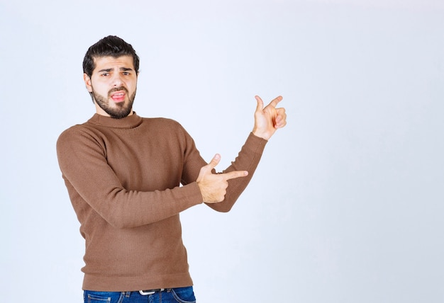 Image of a young handsome man model standing and pointing away. high quality photo