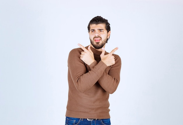 Image of a young handsome man model standing and pointing away with fingers. high quality photo