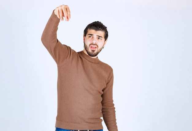 Image of a young handsome man model standing and pointing down. high quality photo