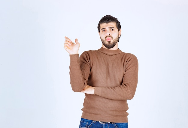 Image of a young handsome man model standing and pointing up . high quality photo