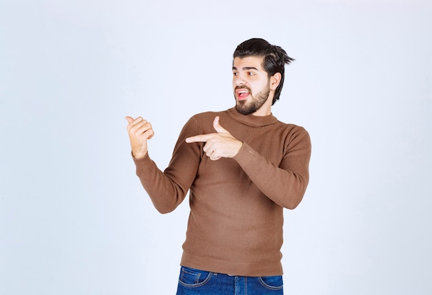 Image of a young handsome man model standing and pointing up with fingers. high quality photo