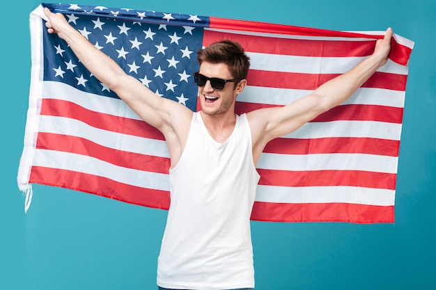 Image of young handsome man standing over blue isolated  holding usa flag. looking aside.