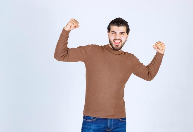 Immagine di un giovane uomo bello in piedi e mostrando i suoi muscoli. foto di alta qualità