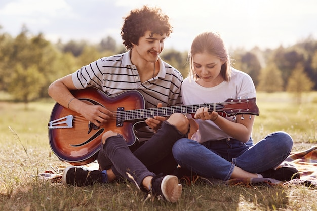 Image of young handsome man with dark curly hair teaches playing guitar her friend, couple have picnic in meadow, have romantic, enjoying spending time together, hot sunny summer day. youth concept.
