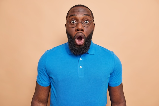 Image of young handsome shocked man with thick beard stares bugged eyes hears unexpected bad news wears round spectacles blue t shirt isolated over beige wall
