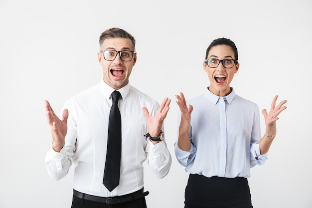 Image of young happy business colleagues couple isolated over white wall make winner gesture.