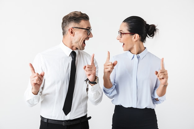 Image of young happy business colleagues couple isolated over white wall pointing.
