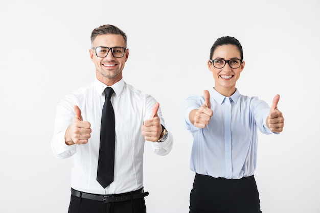 Image of young happy business colleagues couple isolated over white wall showing thumbs up.