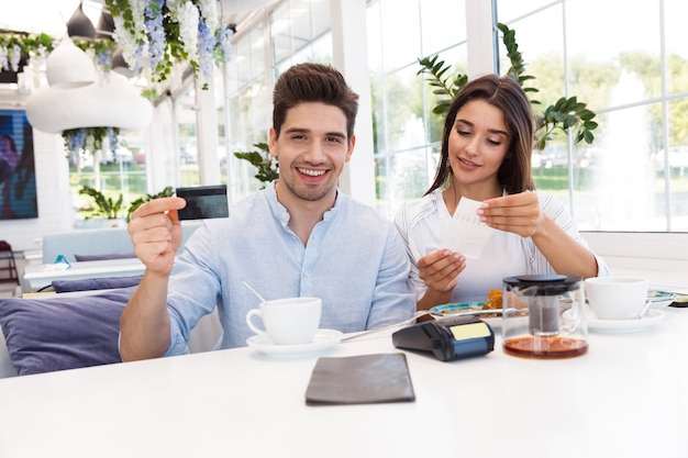 Image of a young happy loving couple sitting in cafe holding credit card and check.