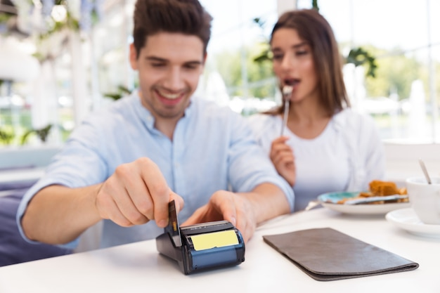 Image of a young happy loving couple sitting in cafe holding credit card and make payment.